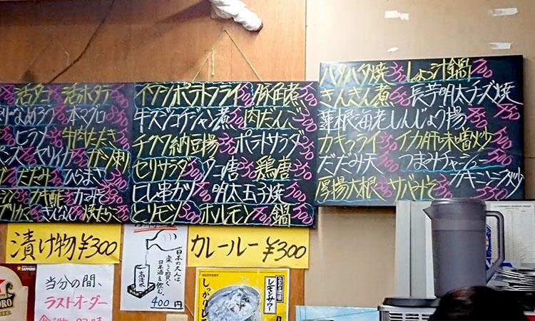アテのメニューがたくさん。別の壁には日本酒メニューと定食メニュー。